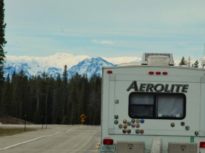RV driving on road toward mountains with National Parks stickers